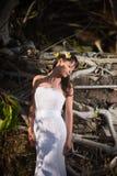 摆在石墙背景的热带树中间的新娘 免版税库存图片