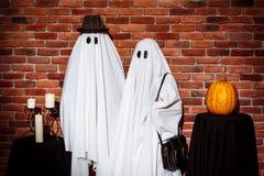 摆在砖背景的鬼魂夫妇  万圣节当事人 库存图片