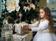 摆在礼物的白色礼服的逗人喜爱的小女孩 库存图片