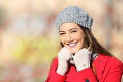 摆在秀丽的妇女温暖地穿衣在冬天 库存图片