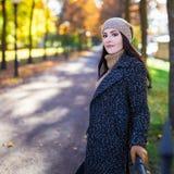 摆在秋天公园的可爱的妇女 库存图片
