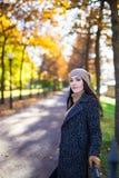 摆在秋天公园的愉快的可爱的妇女 图库摄影