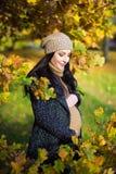 摆在秋天公园的愉快的美丽的孕妇 免版税图库摄影