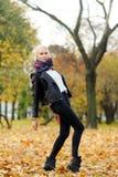 摆在秋天公园的白肤金发的女孩在温暖的天 免版税库存照片