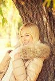 摆在秋天公园的美丽的典雅的微笑的白肤金发的妇女站立在树附近 图库摄影