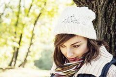 摆在秋天公园,季节性烦恼的年轻youful深色的妇女 免版税库存照片