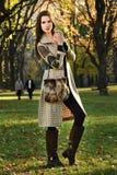 摆在秋天时尚的中央公园的有吸引力的年轻模型 图库摄影
