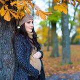 摆在秋天森林里的美丽的孕妇 免版税库存照片