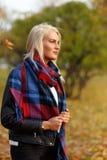 摆在秋天森林里的美丽的白肤金发的妇女 免版税库存照片
