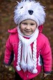 摆在秋天森林里的逗人喜爱的小女孩 图库摄影
