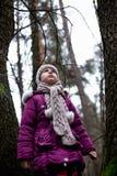 摆在秋天森林里的逗人喜爱的小女孩 免版税库存图片