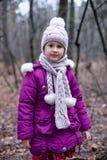 摆在秋天森林里的逗人喜爱的小女孩 免版税图库摄影