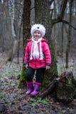 摆在秋天森林里的逗人喜爱的小女孩 免版税库存照片