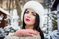 摆在积雪的树下的女孩画象 库存照片