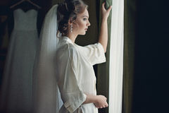 摆在窗口,婚姻的准备附近的长袍的美丽的新娘 库存照片