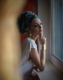 摆在窗架的白色女衬衫的可爱的性感的夫人看外面 肉欲的少妇画象有头巾的 免版税库存照片
