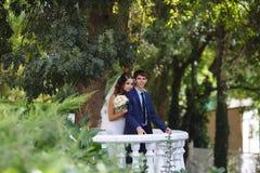 摆在站立在一个白色阳台的一对新婚的夫妇在庭院里 新娘走向新郎从后面 图库摄影
