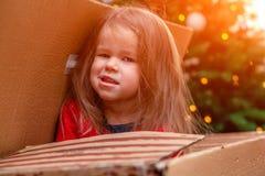摆在箱子的快乐的恶作剧女孩从圣诞节下面 免版税库存照片