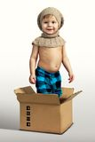 摆在箱子的男孩 免版税库存图片