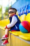 摆在篮球场的时髦的小男孩 库存图片