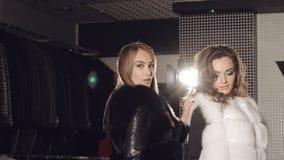 摆在精品店的富有的皮大衣的两个模型做广告的 迟缓地 影视素材