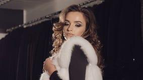 摆在精品店的富有的皮大衣的愉快的妇女照相机的 影视素材
