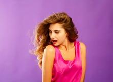 摆在紫罗兰色背景的演播室的美丽的少妇 f 免版税库存照片