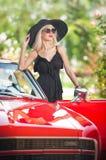 摆在红色减速火箭的汽车附近的时髦的白肤金发的葡萄酒妇女室外夏天画象  时兴的可爱的公平的头发女性 免版税库存照片