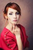 摆在红色礼服的时髦的女人 免版税库存照片