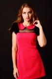 摆在红色礼服的肉欲的美丽的白肤金发的妇女 长期卷曲女孩头发 图库摄影