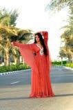 摆在红色街道妇女的美丽的礼服 免版税库存图片
