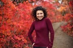 摆在红色autumnn灌木的照相机的红色sweather的年轻黑发妇女 库存照片