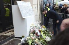 摆在纪念品前面的年轻人一朵花Bataclan攻击的周年的 免版税库存图片