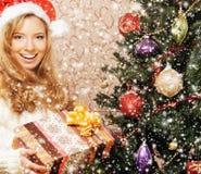 摆在结构树附近的圣诞节帽子的一个女孩 图库摄影