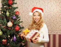 摆在结构树附近的圣诞节帽子的一个女孩 免版税库存照片