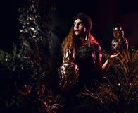 摆在绿色礼服的美丽的时尚卷发妇女在热带叶子森林里用大金菠萝果子 库存照片
