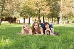 摆在美丽的少妇,当说谎在格子花呢披肩在公园时 免版税库存照片