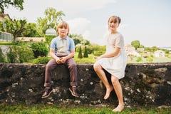 摆在美丽的庭院里的时尚孩子 免版税库存图片