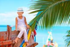 摆在老小船的逗人喜爱的时兴的男孩在热带海滩 免版税库存图片
