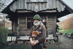 摆在老木小屋前面的老有胡子的林务员 免版税库存图片