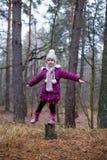 摆在老树桩附近的小女孩在秋天森林里 库存照片