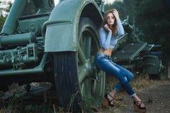 摆在老火炮附近的年轻性感的模型 库存图片