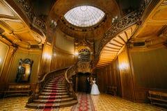 摆在老经典豪宅华美的富有的内部的新婚佳偶  免版税库存照片