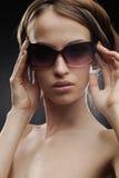 摆在肉欲的太阳镜的女孩 免版税库存图片
