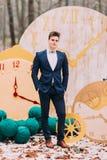 摆在背景的秋天森林装饰时钟的英俊的新郎 免版税库存照片