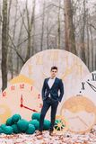 摆在背景的秋天森林装饰时钟的英俊的新郎 免版税库存图片
