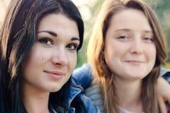 摆在胳膊的两个美丽的年轻朋友胳膊 库存图片