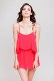 摆在臀部和看的桃红色套衫连超短裙的发笑美丽的少妇 免版税库存图片