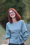 摆在自然绿色领域的美丽的年轻红头发人妇女 免版税库存照片