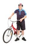 摆在自行车旁边的高级自行车骑士 免版税库存照片